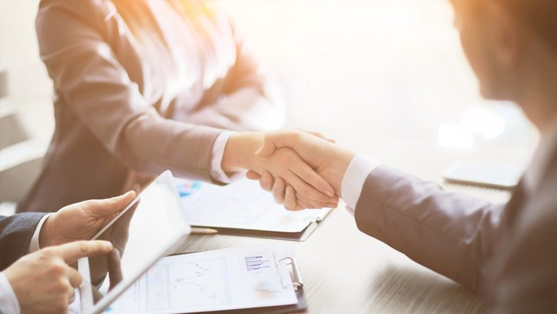 Man and woman shaking hands across business desk