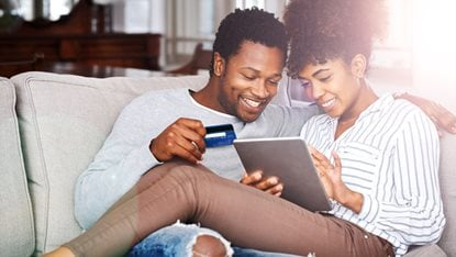 Couple with credit card and tablet