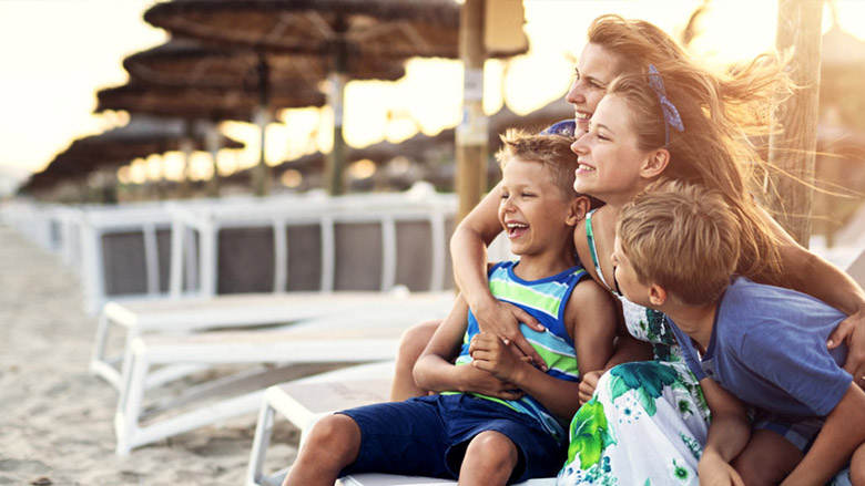 Mom with three kids in chairs on beach