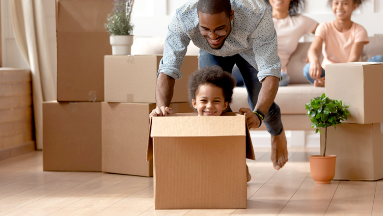 dad pushing young son in a box at new home